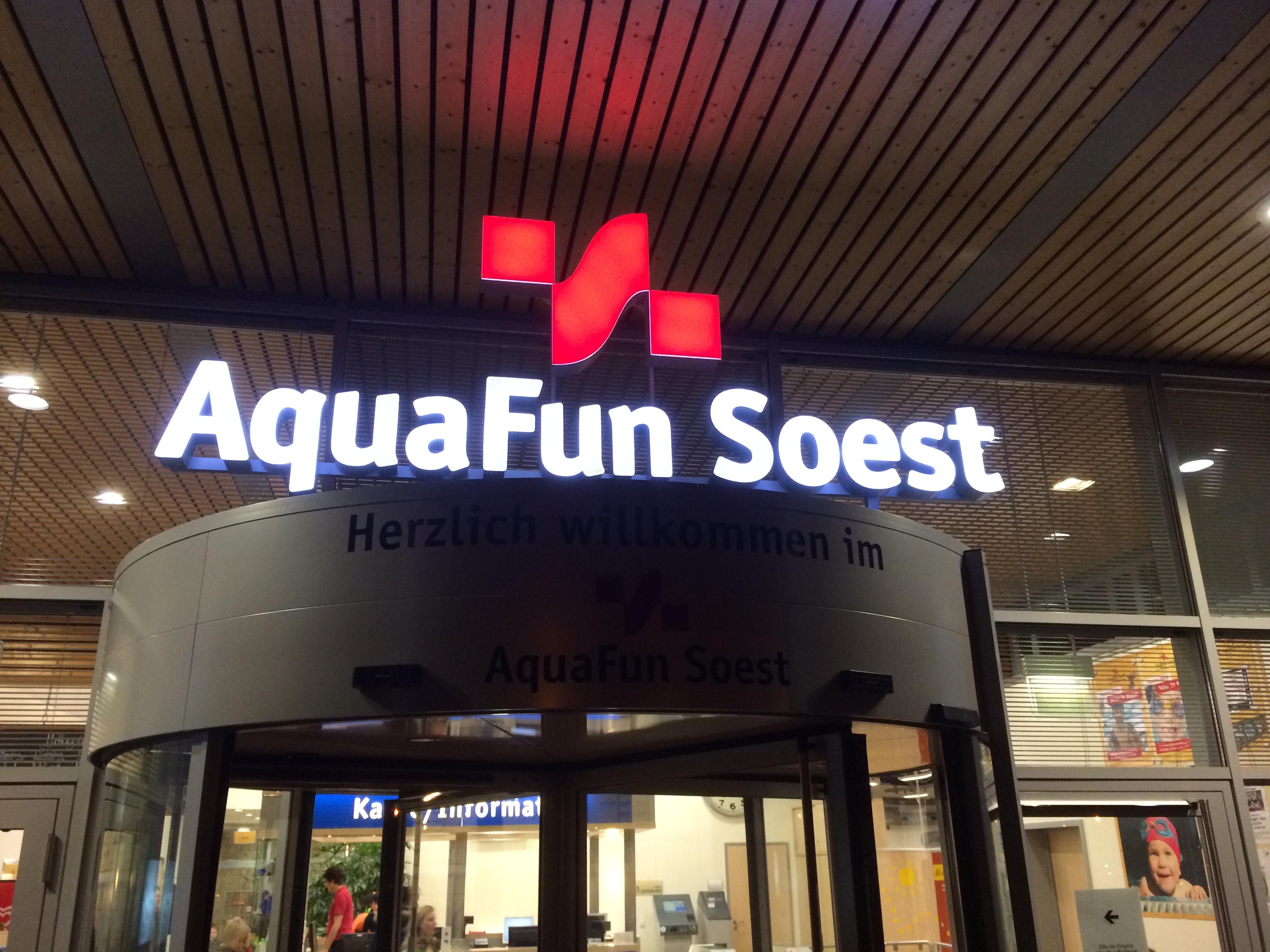 Aquafun in Soest, Eingang mit leuchtender Wort-Bildmarke bei Nacht