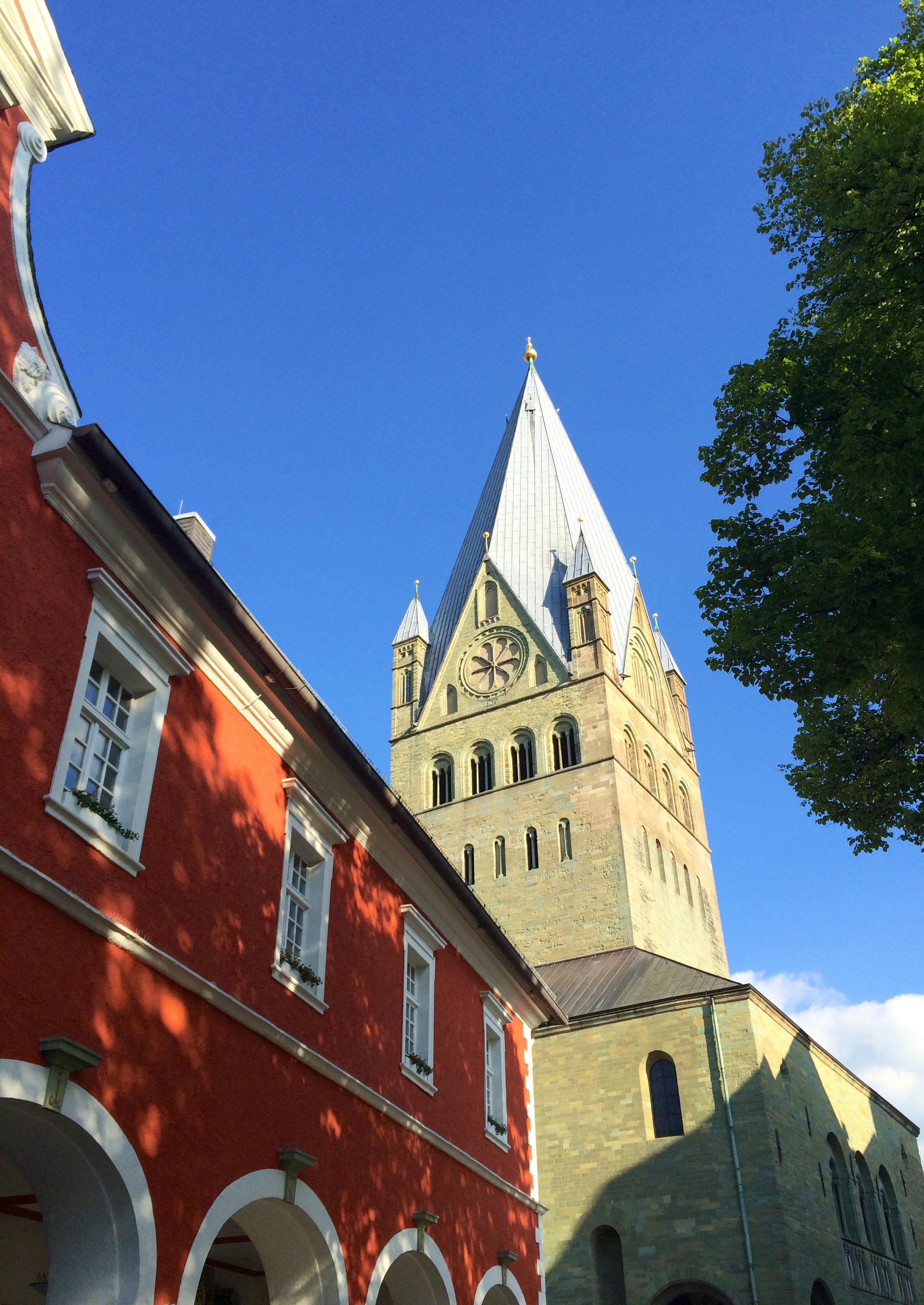 Altstadt von Soest mit Haus mit roter Fassade und Kirchturm im Hintergrund vor blauem Himmel